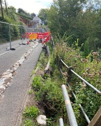 This picture shows a road barrier that has slipped from the side of the road due to the landslip. It is cordoned off.